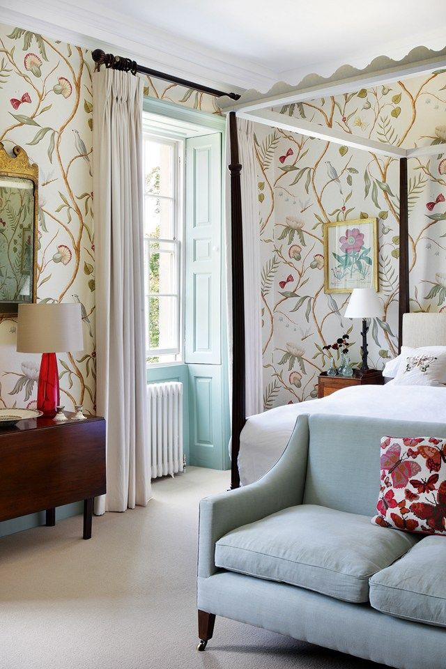 In a spare room, an elegantly simple four-poster bed from Max Rollitt ensures the focus is on the 'Adam's Eden' wallpaper from Lewis & Wood.