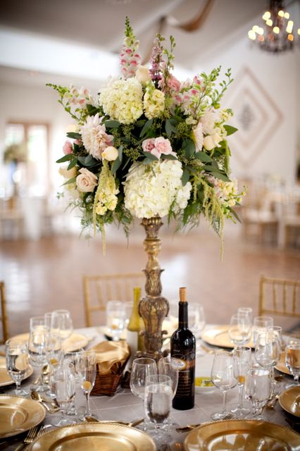 Elevated design of cream hydrangea, pale yellow stock, appleblossom pink snapdragons, pink larkspur, cafe au lait dahlias, pink roses, and green hanging amaranthus.