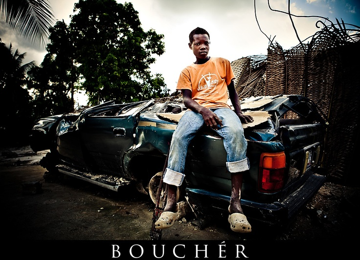 Pictured: Earthquake Damage, Leogane, Port Au Prince, Haiti, Photos by: © Weston Bouchér, http://www.BoucherPhotography.com/blog, Non-Profit Photography, Humanitarian, Children of the Nations, Flood Church, crushed car, crushed truck, boy sitting