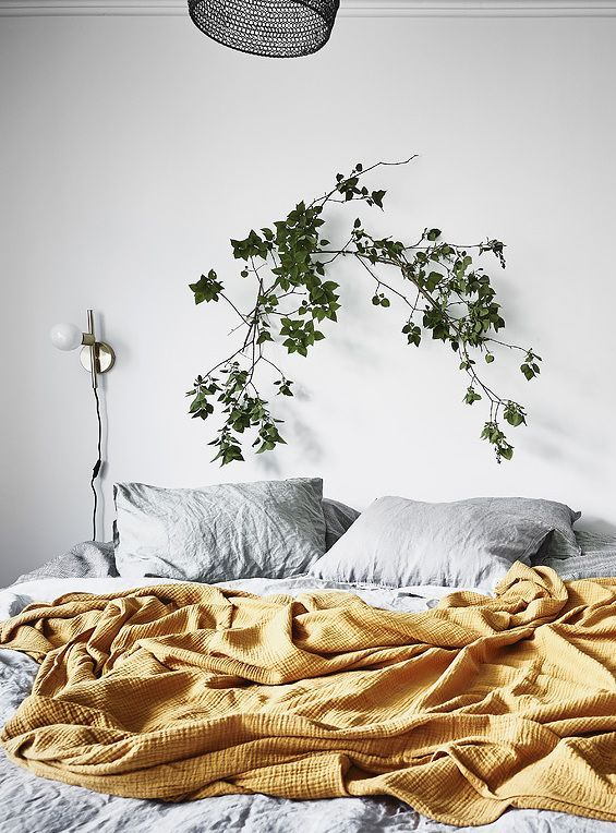 Beautifully styled home - via Coco Lapine Design Blog. Bedroom interior goals. Love the mustard yellow throw blanket against the grey duvet and white walls. Topped off with stunning greenery and a stylish lamp fixture.