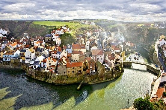Beautiful English Town Nestled On The Banks Of A Curling Green River Below The Plateau Roof