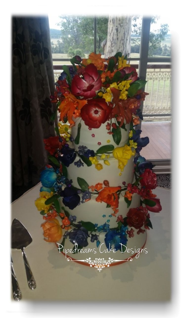 A stunning brightly coloured wedding cake. with the sugar flowers wrapping each tier and an amazing cluster of flowers to top off the cake.