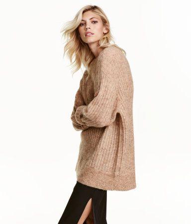 Beigemelert. PREMIUM QUALITY. En ribbestrikket, oversized genser i melert ullblanding med mohair. Genseren har rund halsringning, lange ermer og lav