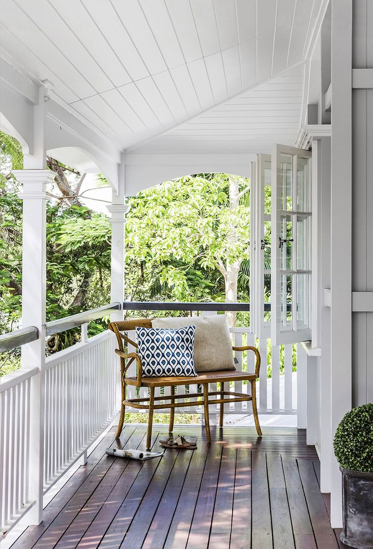Queenslander veranda: white painted wood railing/balustrade, timber decking, white wood panelling on ceiling, French windows, leafy outlook