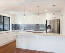 Sleek handle-free cabinetry, Metaline splashback, white stone benchtop with undermount sink, with servery window through to outdoor entertaining area.