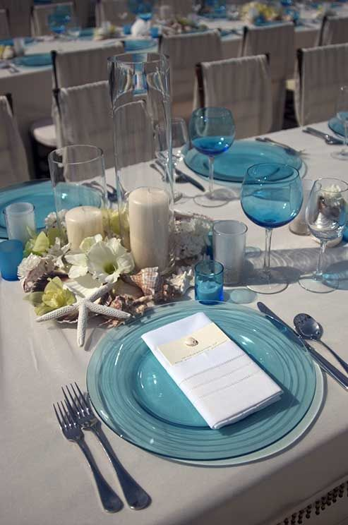 Embrace nature with shells, neutral linens and scattered blooms, with transparent blue chargers and glassware for a pop of color.