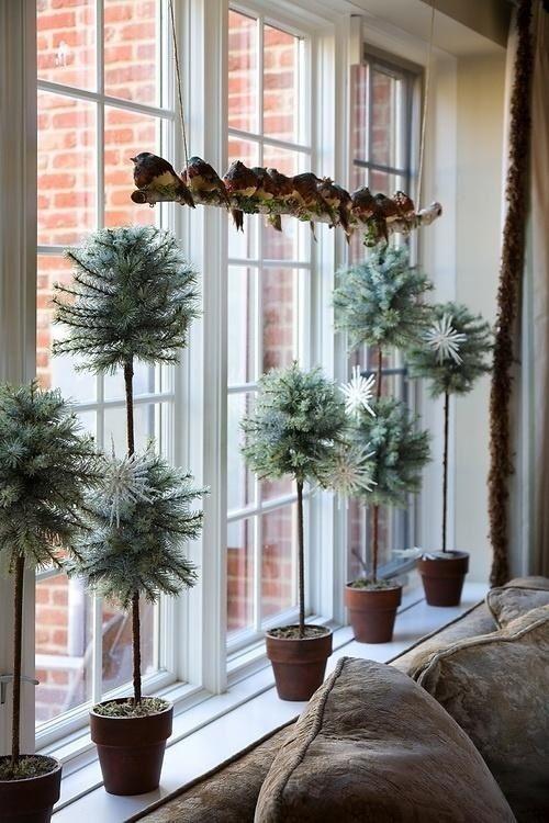 Искусственные елочки разной высоты в горшочках украшают этот подоконник. .