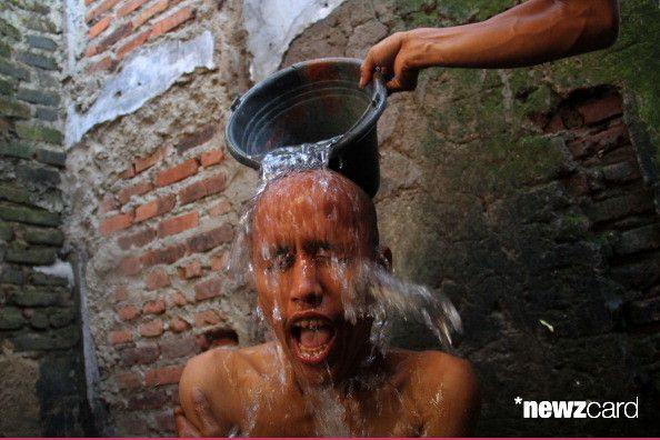 An officer throws water onto a mental health patient at a shaman clinic on May 10, 2014 in Tasikmalaya, Indonesia. Pour water on a regular basis to patients part of therapy. The Mentari Hati Foundation set up the mental health rehabilitation centre in a former bus terminal. They largely take in patients with mental health issues who have no support network. A shortage of trained health workers, lack of treatment options and widespread misconceptions about mental illness in Indonesia have led…