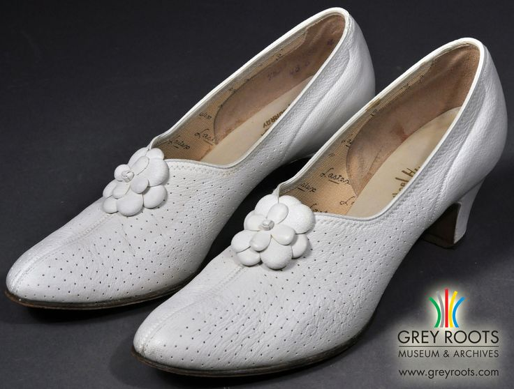 """A pair of ladies', white leather, """"Heel Hugger"""" pumps made by Murray and purchased at Scarrow's in Owen Sound, Ontario. The leather is perforated with many small air holes. To prevent slipping, the otherwise leather soles have cork grips nailed onto the heels. Grey Roots Museum & Archives Collection."""