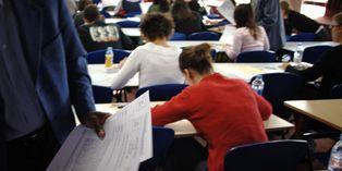 Un surveillant distribue le sujet du bac de philo dans une classe du lycée Aragon, le9juin2005 à Givors.