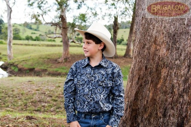 Boys Western Shirt | Blue Paisley Shirt | Brigalow Country ClothingOur boys shirts are built tough - to survive boys. This 100% cotton, silvery blue coloured paisley print boys shirt is one of two in a series, and is also available in matching Mens sizes. The blue/silver/black paisley combination pattern not only looks great for dressy occasions, but also helps mask any scuff or dirt marks that country boys have a talent for accruing just before photo time.