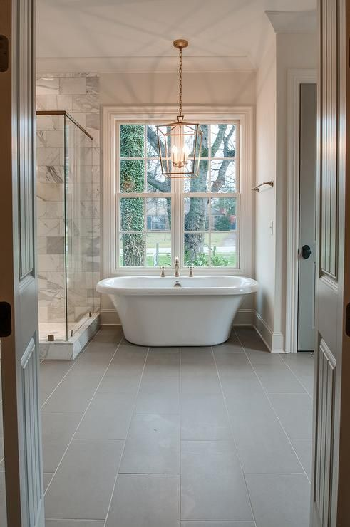 Chic bathroom features a Darlana Lantern in Antique Brass hanging over a freestanding tub placed atop a gray porcelain tiled floor flanked by a glass walk in shower to the left and a water closet finished with a gray door to the right.
