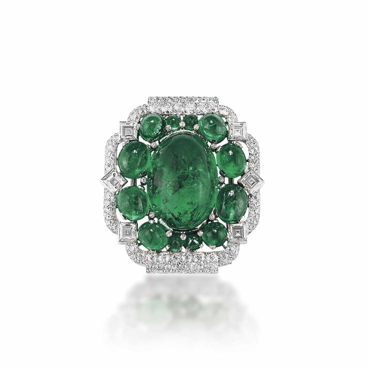 AN ART DECO EMERALD AND DIAMOND BROOCH, BY CARTIER Centering upon a cabochon emerald within smaller cabochon emerald surround, to the pavé-set diamond frame enhanced by square-cut diamond collets, 1930s, 5.0 cm, with French assay mark for platinum Signed Cartier, no. 6483