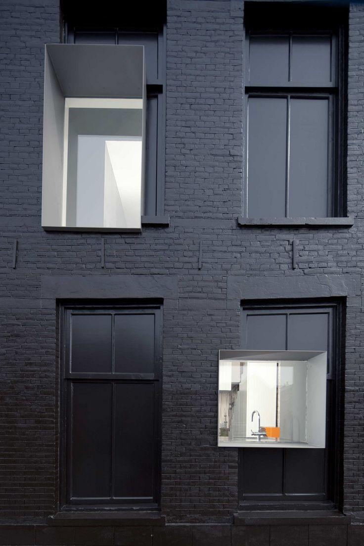 De 100 jaar oude gevel van de woning is volledig geschilderd in een glimmende zwarte olie.