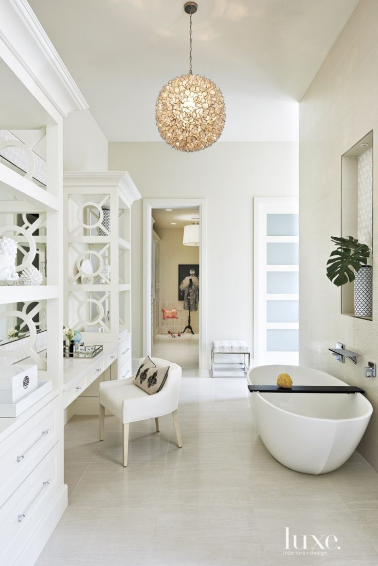 1: A Mediterranean Neutral Bathroom in Scottsdale, AZ  The launching point for the master bathroom's vanity area came from the streamlined Wetstyle tub outfitted with chrome Hansgrohe hardware. A handmade capiz-shell chandelier by Horchow imparts femininity and a soft glow.