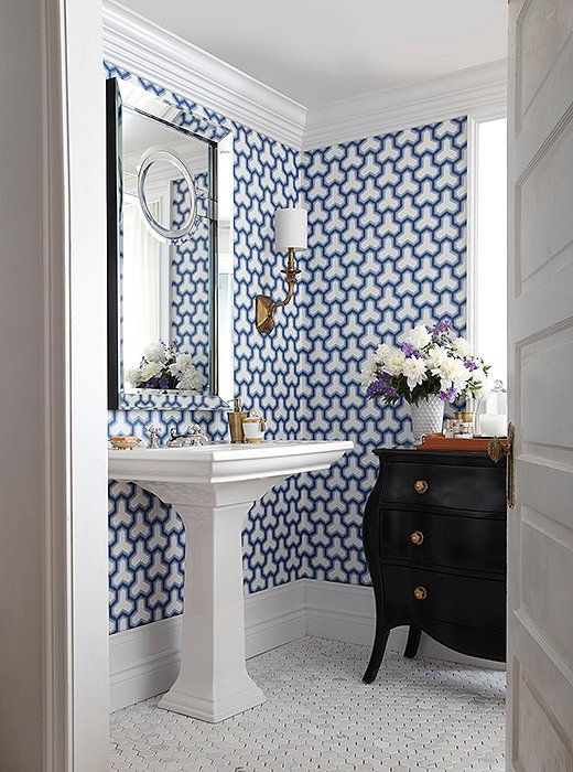 Bold blue and white graphic patterned wallpaper transforms this small powder room into a total standout—something your guests won't soon forget.