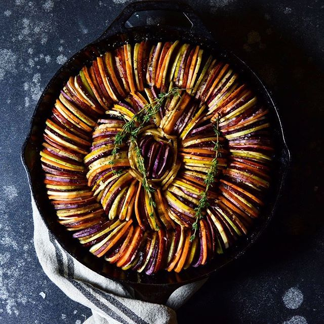 Root Vegetable Tian. I sliced up (did use a mandolin) two varieties of purple sweet potato (Okinawa and Stokes), Japanese sweet potato, garnet yam, celery root, carrot, sunchoke, rutabaga, golden and red beets and a few parsnip slices scattered throughout. I coated it with a thin layer of olive oil and flaky sea salt, fresh ground pepper (lots) and a few sprigs of thyme. All sit on top of a layer of sautéed melted leeks (thank you @chef_seabones for the inspo) Christine, this one is for…