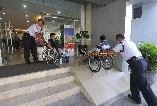 Petugas keamanan membantu nasabah berkusi roda usai melakukan transaksi perbankan di BNI Cabang Fatmawati, Jakarta, Kamis (3/9/2015). Pada 4 September ditetapkan sebagai Hari Pelanggan Nasional. Peringatan bertujuan untuk meningkatkan kesadaran perusahaan dan lembaga publik untuk lebih memahami kebutuhan pelanggan sehingga dapat meningkatkan kualitas layanan kepada masyarakat.