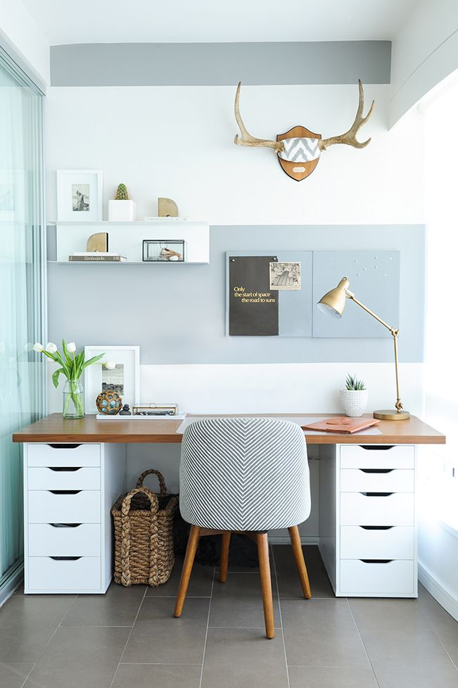 Small home office with gray and white striped wall, wood and white desk,  tile floor and patterned chair Shift Interiors