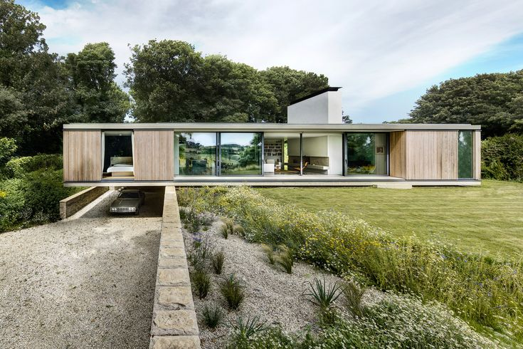 One end of this retirement residence in the English countryside by Ström Architects cantilevers over a wall to protect a parking spot for a vintage car