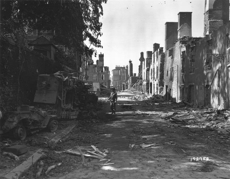 American vehicles were totally destroyed and lying on a sidewalk in the Grande Rue de Mortain.  A returned Half-track M3 and a Jeep that looks calcined armed GI of a Thompson submachine gun M1A1.