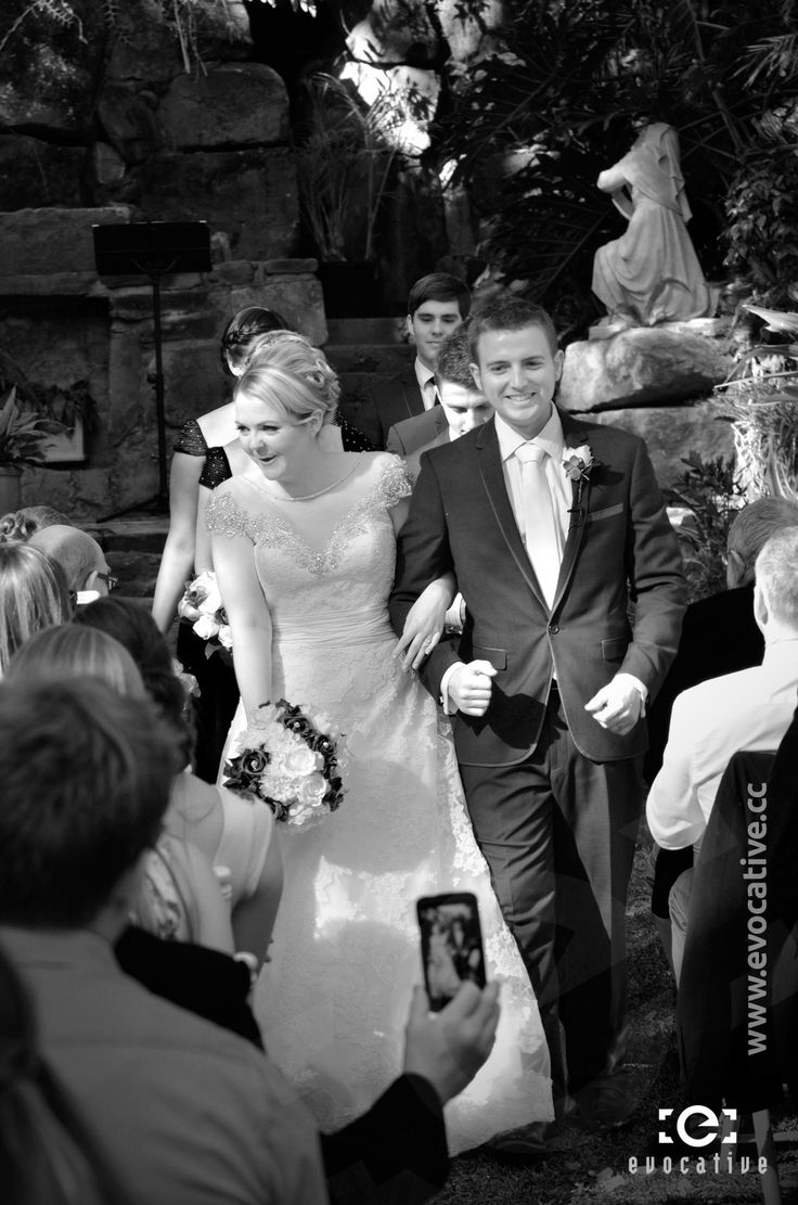 The new happy couple smiling as they walk down the aisle together at Woodlands of Marburg. #WeddingPhotography #BlackAndWhite
