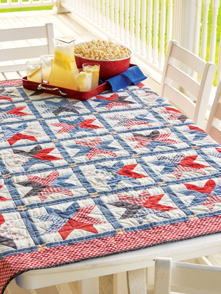 """BRAVEHEART by Emily Bailey: Designer Emily Bailey used red and blue prints to comprise a field of 30 stars. The unique star blocks feature an hourglass unit at their center and are surrounded by contemporary Flying Geese units. Finished size is 52"""" x 61""""."""