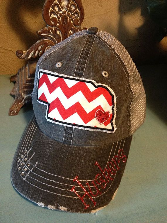 This is a gray trucker baseball hat. If you love Nebraska, glitter and rhinestones, then this is the hat for you! Huskers is added to the brim of the