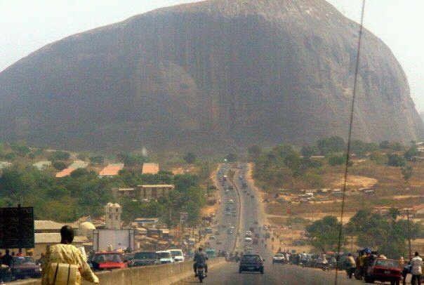 """Zuma Rock  Abuja,Nigeria    Zuma Rock is a large monolith located in Niger State, Nigeria. It is just north of Nigeria's capital Abuja, along the main road from Abuja to Kaduna, and is sometimes referred to as """"Gateway to Abuja."""" It is depicted on the 100 naira bill. Zuma Rock is 725 meters above its surroundings."""