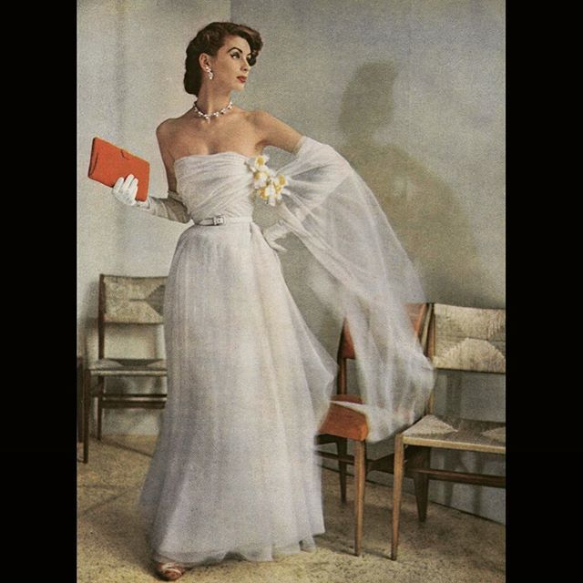 A soft white #christiandior gown that floats around her figure, with a cloud-like wisp of a shawl that is kept in place by a bunch of daffodils pinned to the bodice. Plus - the modern touches that make the statement - #gioponti chairs that cluster behind her, and coral clutch bag and matching lips. #francesmclaughlingill #voguemagazine 1952 #dresshistory #vintagefashion #fashionstudies #fashionhistory #1950sfashion #parisfashion #hautecouture @dior