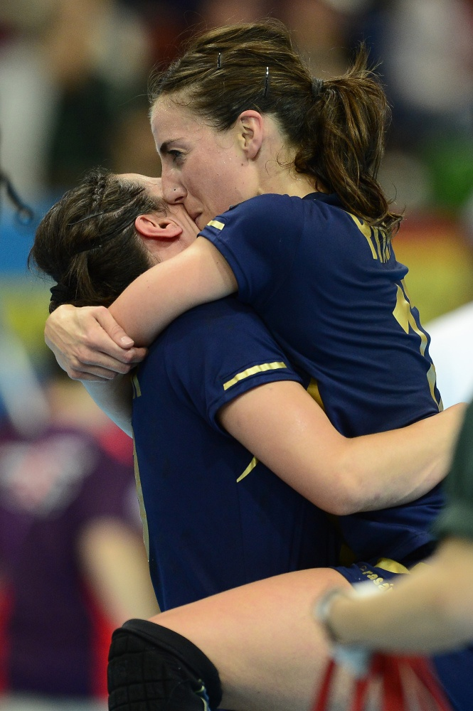 Spain's leftwing Elisabeth Pinedo Saenz (R) kisses a teammate as she celebrates their victory over Sweden at the end of the women's preliminary Group B handball match Spain vs Sweden for the London 2012 Olympics Games on August 3, 2012 at the Copper Box hall in London. Spain won 25-24.