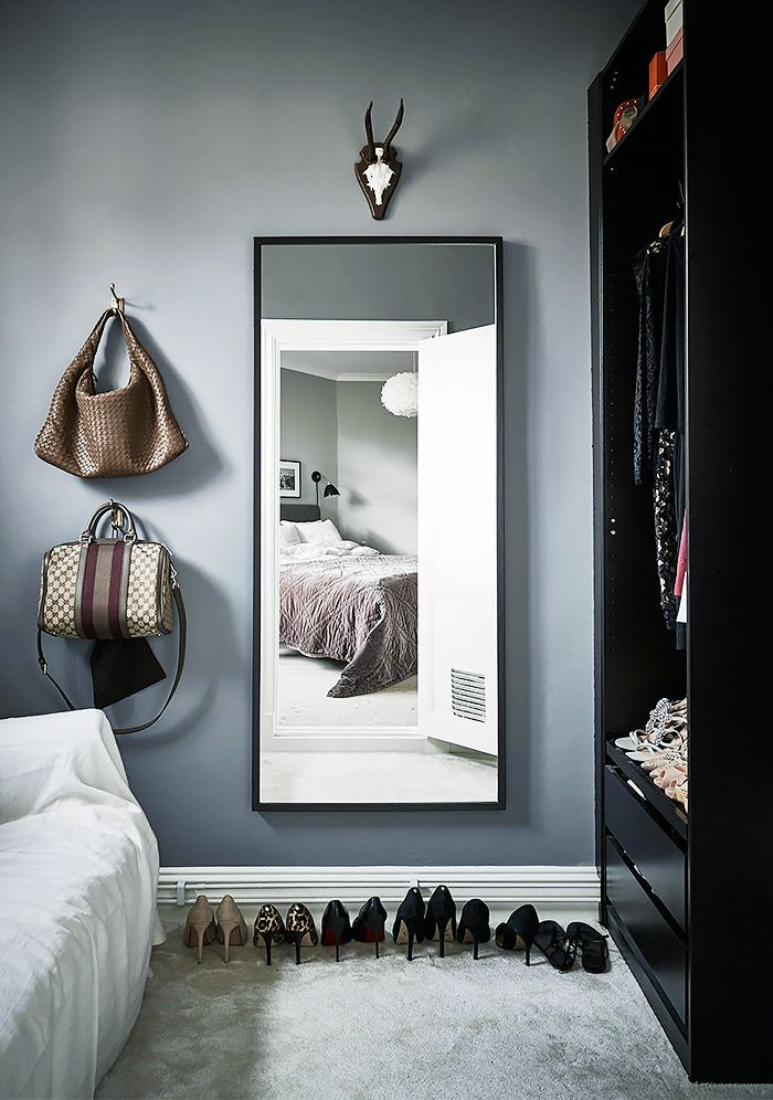 A built-in black closet looks great with a sleek mirror and lined up accessories