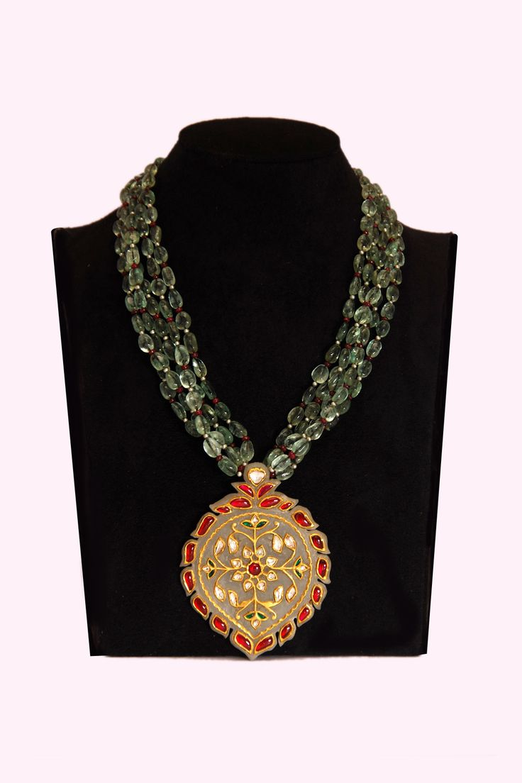 Subtle yet stunning, the gold necklace is a statement masterpiece exclusively set in gold. It is beautifully textured with a tasteful combination of multiple green emerald beads strand and faceted with jade carving etched with uncut diamond, rubies and emerald lending a bold finish to your overall look. It comes with weight of 24 K Gold - 19.80 Gm, Diamond - 2.71 Ct, Emerald - 622.00 Ct, Ruby - 64.80 Ct and Pearl - 16.30 Ct.