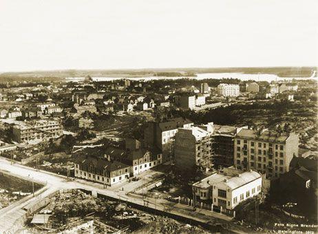 Panoraama Kallion kirkon tornista koilliseen. Vaalea rakennus etualalla oikella on Kallion sähköasema. Keskellä kuvaa kulkeva katulinja vasemmalta oikealle on rakenteilla oleva Helsinginkatu. Signe Brander 1912.