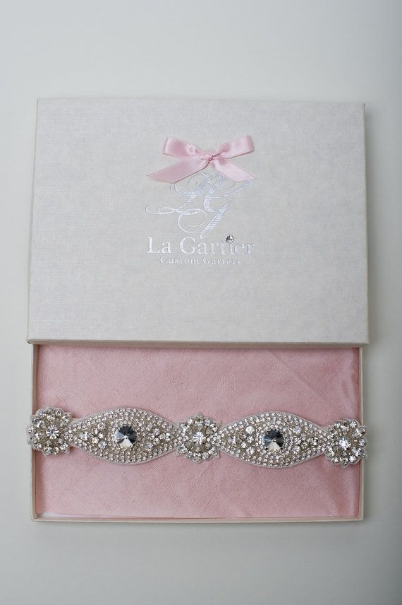 This garter is made out of a solid sparkling rhinestone band. The back half of this garter is made of a light, soft light light ivory elastic and ruffle detail. If you order this garter, please leave us your leg measurement in the comments section of your check out so that we may custom make your garter to fit your leg.  Due to its slim shape, this garter would be perfect with a form-fitting gown (ie: mermaid or trumpet) due to the fact that it lies very flat against the leg. If you would…