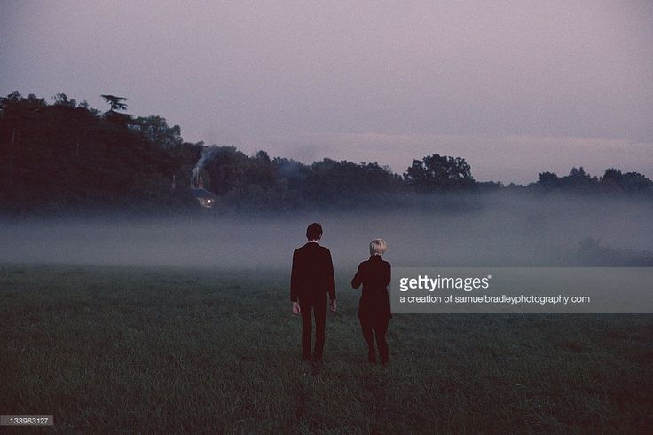 Couple holding hands in misty field wearing black clothing.