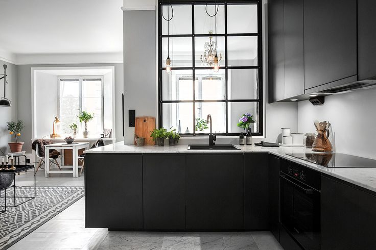 I'm completely in love with this home: the grey walls, the black kitchen and the white floor are...