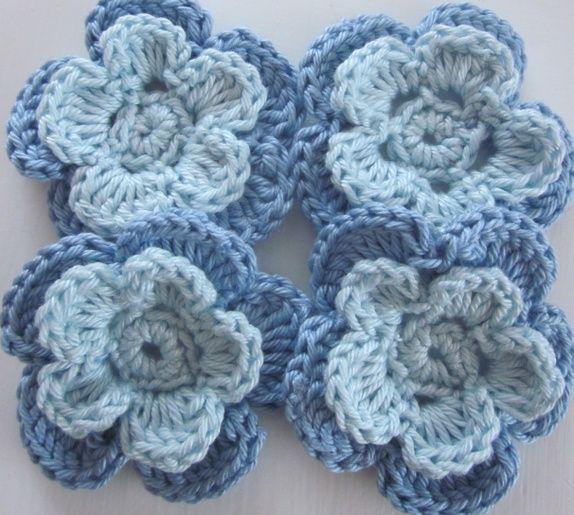 1 Sett med 4 hekla blomster i lys blå og himmelblå.
