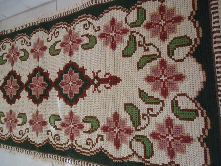 Confeccionado em tecido de Juta, bordado em lã com pontos Arraiolo e Cruz. Franja tecida no tear. A franja está incluída na medida do tapete.  Altura: 1 cm  Largura: 70 cm  Comprimento: 1,55 m  Peso: 2,5 Kg