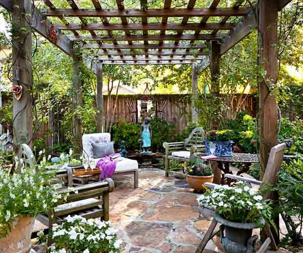 upgrade outdoor room, pergola with stone floor, wall, water element, container plants and outdoor furniture