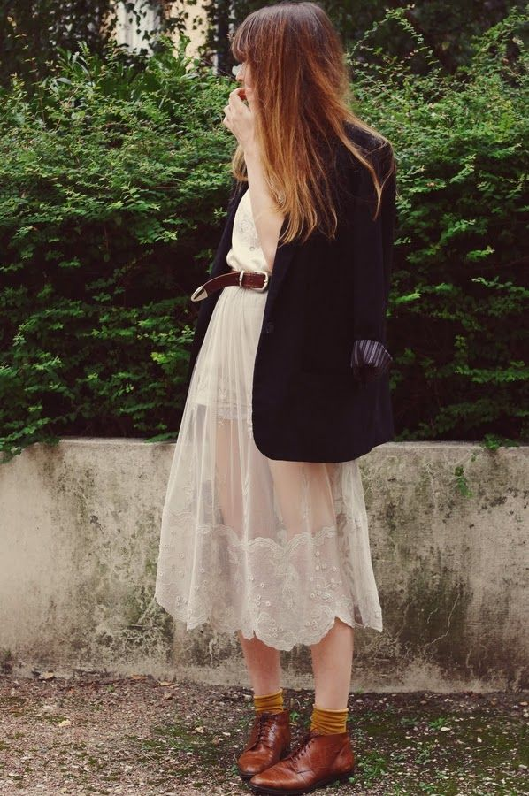 """lady moriarty dans un look vintage sur la base d'une robe romantique blanche et transparente qu'elle a réussi à """"casser"""" et rendre portable plus facilement au quotidien en la portant avec une veste et l'accessoirisant avec une ceinture vintage en cuir brun, et des chaussettes moutarde qui dépasses des bottines en cuir brun"""