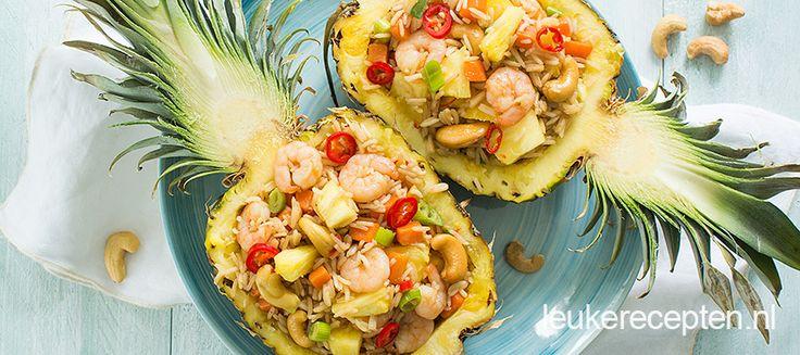 Gebakken rijst met garnalen en groenten geserveerd in een bakje van ananas. Op deze manier serveer je een indrukwekkend en zomers gerecht aan je gasten.