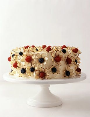 Cake with flowers made from raspberries, blueberries, and almond slices.