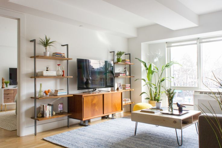 """The <a href=""""http://www.cb2.com/saga-credenza/s141359"""" target=""""_blank"""">media console</a> is framed by two <a href=""""http://www.cb2.com/helix-acacia-bookcase/s328328"""" target=""""_blank"""">bookshelves</a>. Also, can we note how many plants are in this apartment? They're just everywhere."""