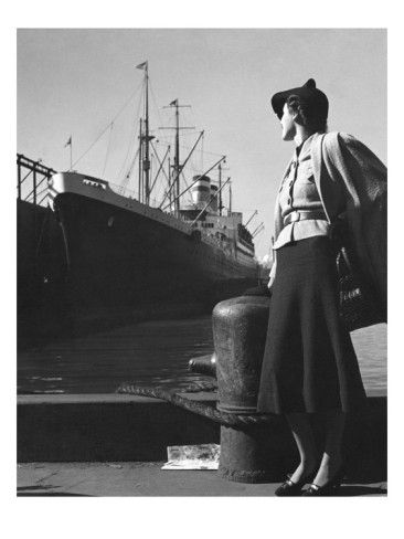 Vogue - December 1936    As the ocean liner Hansa prepares to leave port, a model looks on longingly. She wears a wool mesh cape over a belted jacket, with a dark blouse and skirt. She holds a black alligator bag by Koret. The dramatic composition and sense of plot make this work reminiscent of a film still. Toni Frisell's photograph appeared in the December 15, 1936, Vogue.