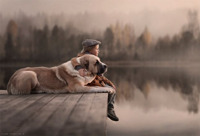 Elena Shumilova's magical, wintry photography: Boy and dog on lake dock - Russian photographer