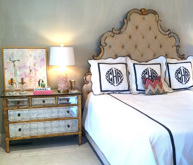 black & white monogrammed bedding, tufted regency headboard, and mirrored & gilt nightstand.