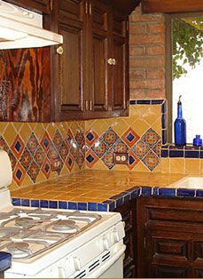 Talavera tile and decorative accents . Love the patterns, colors and brick combo.