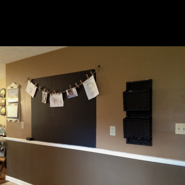My family message center. Chalk board wall with a rope strung across the top to hang pictures and kids art work using clothes pins. On the chalk board we write notes and s weekly menu. We also have baskets for mail and a calendar. All to keep our family organized.