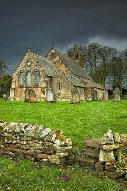 An old church under a dark sky in Northumberland, England